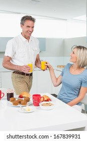 Happy couple with orange juices having breakfast in the kitchen at home