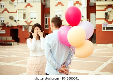 Happy couple outdoors man prepared surprise for a woman. Woman eyes closed, man hiding balloons at his back.