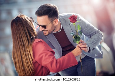 Happy couple outdoors,man give a rose to his girlfriend for Valentine's day.