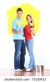 Happy couple painting interior wall of home.