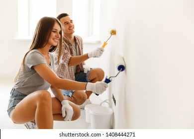 Happy Couple Painting a Wall with a Paint Roller