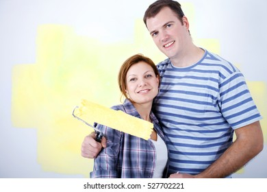 Happy couple painting a wall in their new home. They are smiling and looking at camera.