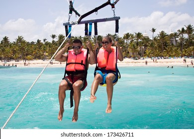 Happy couple Parasailing in Dominicana beach in summer. Couple under parachute hanging mid air. Having fun. Tropical Paradise.
