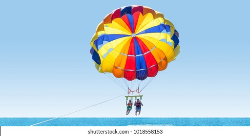 Happy couple Parasailing on Tropical Beach in summer. Couple under parachute hanging mid air. Having fun. Tropical Paradise. Positive human emotions, feelings, family, travel, vacation.
