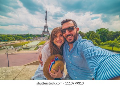 Happy couple in paris, France. Handsome tourist with hat with french flag taking picture selfie traveling in Europe