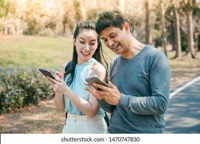 Happy couple in a park using a smart phone online content