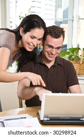 A happy couple paying bills by using online banking at home