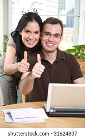 A happy couple paying bills by using online banking at home giving thumbs up