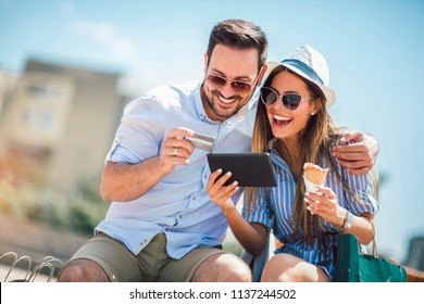 Happy couple paying on line with credit card and digital tablet on the street