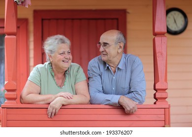 Happy couple pensioners on the porch of a country house