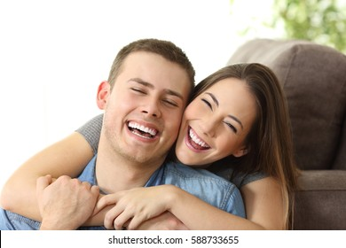 Happy couple with perfect white smile posing and looking at camera on a couch at home