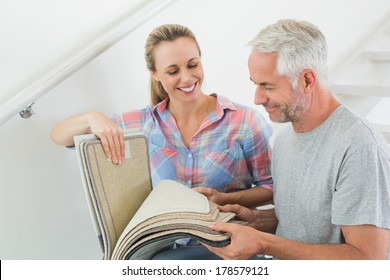 Happy couple picking out carpet samples together in their new home