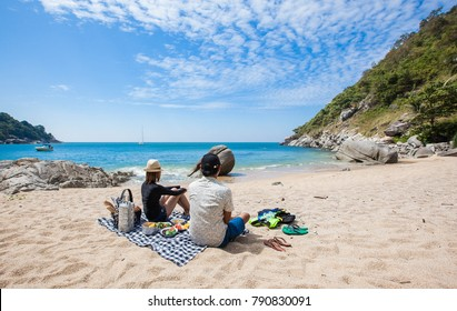 Happy couple picnic on the beach.
