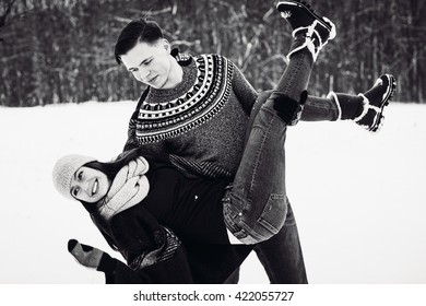 Happy couple playful together during winter holidays vacation outside in snow park b&w