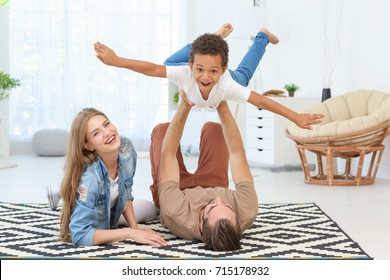 Happy couple playing with adopted African-American boy on carpet at home
