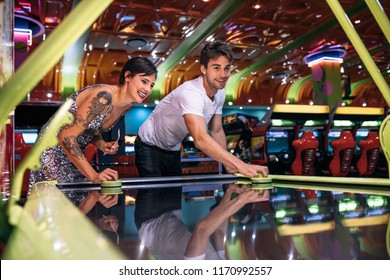 Happy couple playing coin operated air hockey game as a team in a gaming arcade. Friends having fun playing air hockey in a gaming parlour.