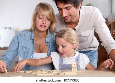 happy couple playing dominos with daughter