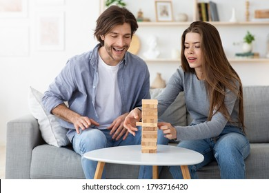 Happy couple playing Jenga while sitting in the living room at home, having fun together