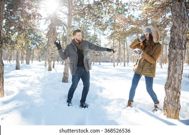 Happy couple playing with snow in winter park. Snowball fight