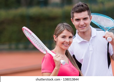 Happy couple playing tennis outdoors and smiling