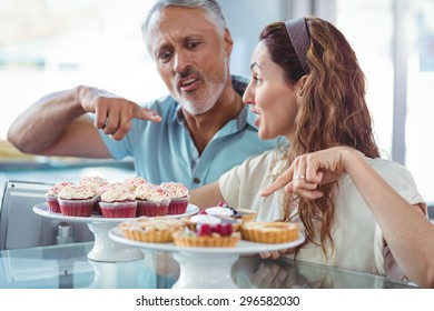 Happy couple pointing cakes in the bakery store