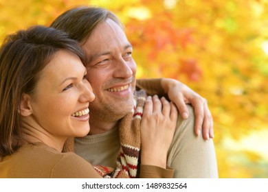 Happy couple posing in autumnal park outdoors