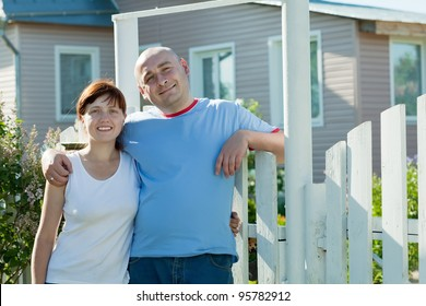 happy couple posing in front of his  home