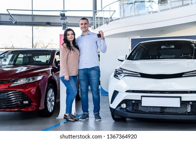 Happy couple posing with keys from new car