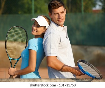 Happy couple posing on tennis court, smiling.