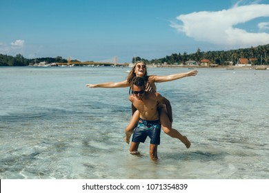 Happy couple posing in the sea, Happy traveling couple making selfie mountains background , sunny summer colors, romantic mood. Stylish sunglasses, straw hat. Happy laughing emotional faces, Bali