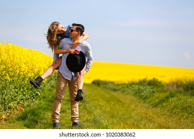Happy Couple posing in the vast field of canola flowers