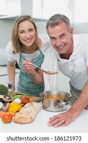 Happy couple preparing food together in the kitchen at home