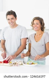 Happy couple preparing salad together in the kitchen