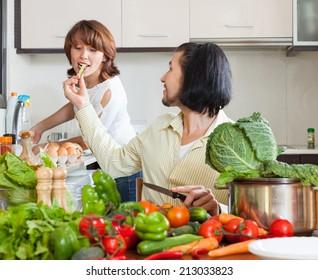 Happy couple preparing vegetable salad in my house