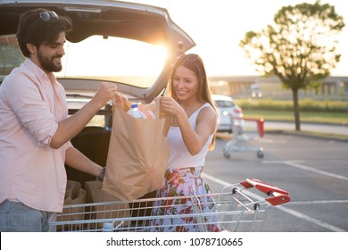 A happy couple puts groceries in his car in front of a supermarket.
