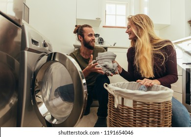 Happy couple putting clothes in washing machine. Couple using a front loading washing machine to wash laundry.