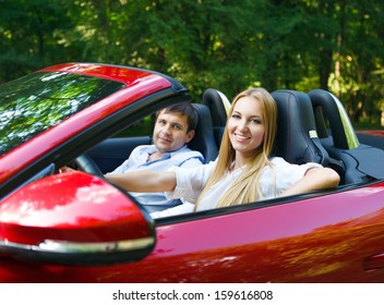 Happy couple in red cabriolet in a sunny day