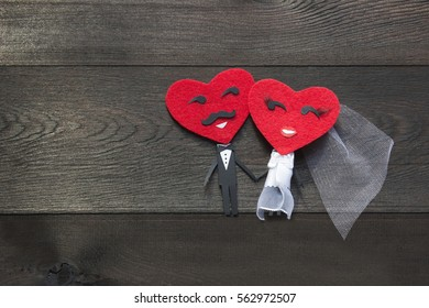 Happy couple of red felt heart faces with black paper bodies on wooden background. Smiling groom and bride, Mister and Missis Hearts in love. Valentines Day and Wedding concept.
