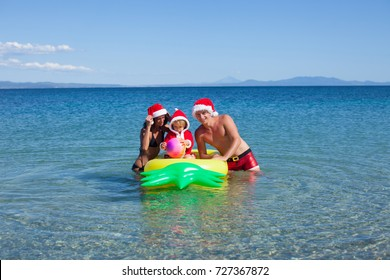 Happy couple in red Santa hats relaxing at romantic tropical beach on sun beds. Christmas or New Year's vacation in hot countries concept. Holiday. Vacation, travel, tourism, adventure. Summer time.