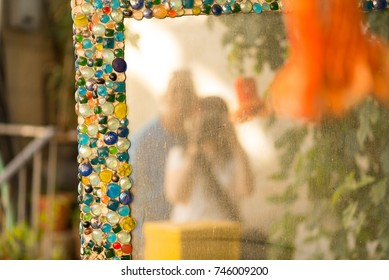 A happy couple is reflected in an old dusty mirror with glass pebbles outdoor.A woman photographs a camera their family, makes selfie on a city street.