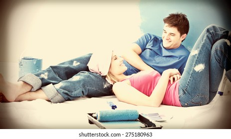 Happy couple relaxing after painting a room in their new house