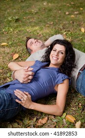 A happy couple relaxing laying in the grass - sharp focus on the woman