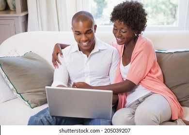 Happy couple relaxing on the couch with laptop at home in the living room