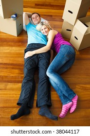 Happy couple relaxing on the floor with boxes around. Moving house