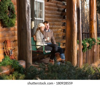 Happy Couple Relaxing on Log Cabin Porch