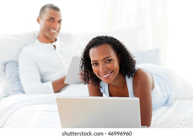 Happy couple relaxing on their bed at home