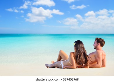 Happy couple relaxing sun tanning on vacation beach lying down on white sand looking at ocean copyspace background. Sunbathing on holiday.