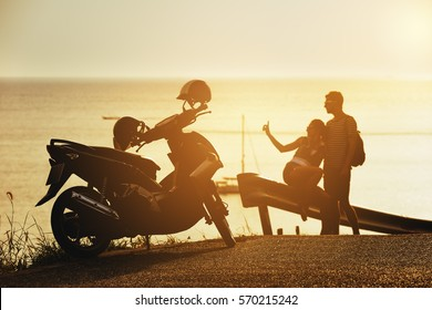 Happy couple relaxing at sunset time on sea backdrop near motorcycle on the border of road. Travel concept