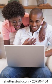 Happy couple relaxing together on the couch using laptop at home in the living room