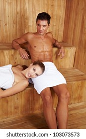 Happy couple relaxing together in a sauna